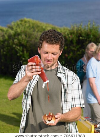 Man pouring ketchup onto hot dog Stock photo © IS2