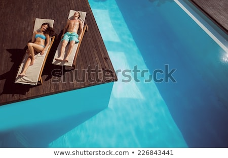 couple lying on sun lounger by pool stock photo © is2