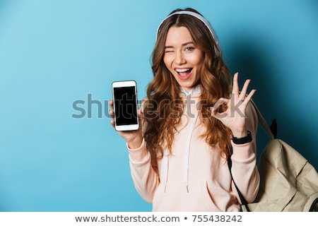 Portrait of a positive young girl holding mobile phone stock photo © deandrobot