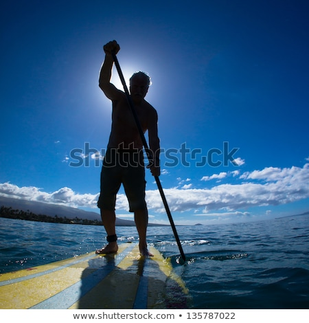 handsome young man on a paddle board stock photo © lightpoet