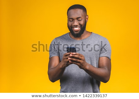 Portrait of african american man smiling and holding smartphone, Stock photo © deandrobot