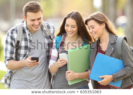 women friends students walking in the park using mobile phone stock photo © deandrobot