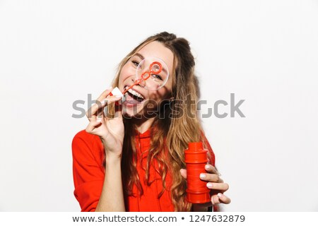 image of european woman 20s wearing red sweatshirt blowing soap stock photo © deandrobot