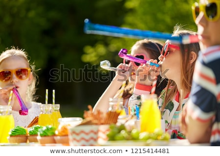 happy kids blowing party horns at summer birthday Stock photo © dolgachov
