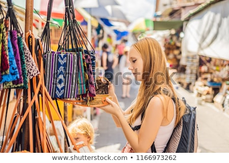 Shopping on Bali. Young woman chooses Famous Balinese rattan eco bags in a local souvenir market in  Stock photo © galitskaya