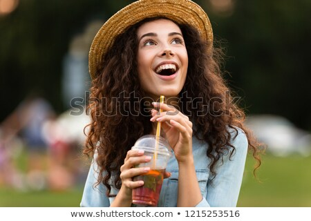 Image of joyous woman 20s wearing straw hat, smiling and drinkin Stock photo © deandrobot