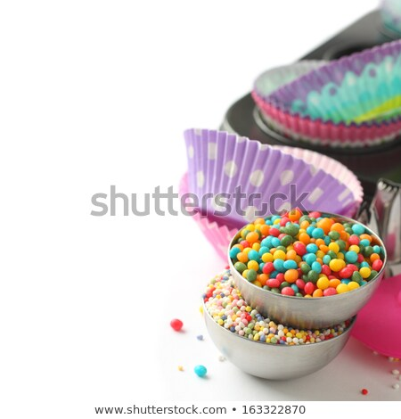 candy sprinkles with cupcake cases and baking pan over white stock photo © melnyk