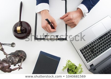 Male lawyer working with contract papers and reading law book in Stock photo © snowing