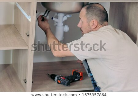 Male Plumber Fixes Sink Siphon In Kitchen Stock photo © AndreyPopov