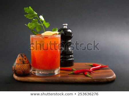 Bloody Mary with ice cubes with celery in bar on black Stock photo © dla4