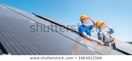 Worker and manager of solar farm looking into the sun Stock photo © Kzenon