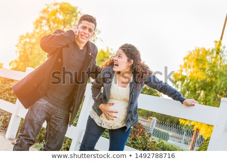 Stunned Hispanic Pregnant Young Couple In Pain Walking Outdoors Stock photo © feverpitch