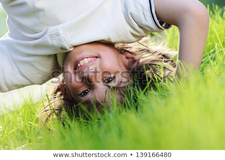 portraits of happy kids playing upside down outdoors in summer park walking on hands stock photo © galitskaya