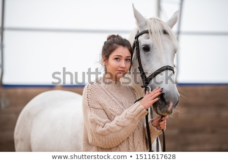 Calm young casual woman in knitted sweater standing by white purebred horse Stock photo © pressmaster