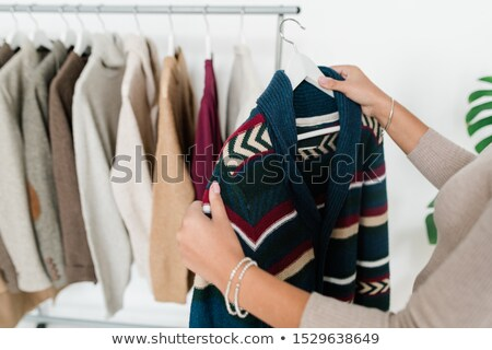 young woman holding hanger with new warm knitted cardigan stock photo © pressmaster