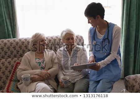 Front view of female doctor and senior women discussing over digital tablet in living room on sofa a Stock photo © wavebreak_media