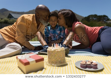 Front view of African American grandmother and grandfather kissing their grandson while celebrating  Stock photo © wavebreak_media
