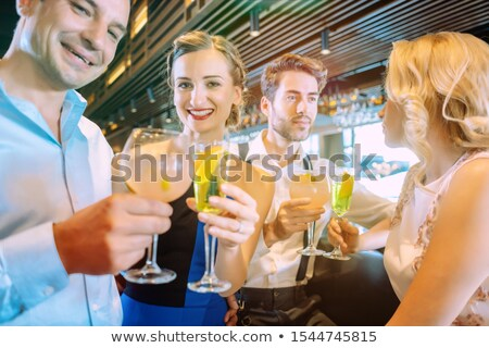Friends enjoying the bar and drinking sugary alcoholic beverages Stock photo © Kzenon