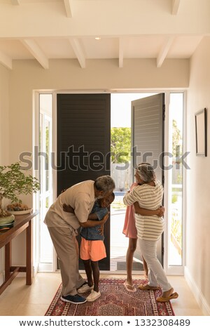 Front view of happy African American grandparents embracing their grandchildren at home Stock photo © wavebreak_media