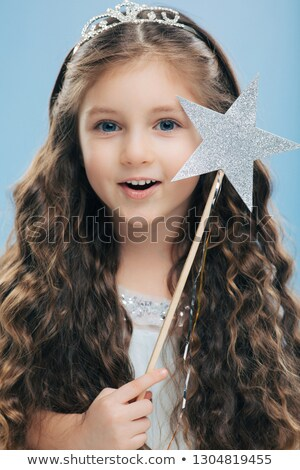 Close up shot of adorable blue eyed small European female princess has long wavy hair, wears crown,  Stock photo © vkstudio