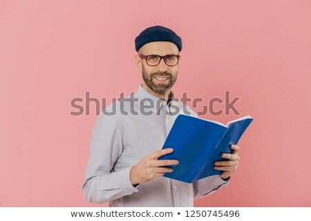 Cheerful unshaven clever man holds book in front reads exciting story, studies scientific literature Stock photo © vkstudio