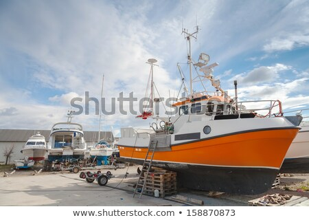 Sailboat and small boat on dry dock by the sea Stock photo © xbrchx