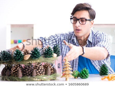 Young man making christmas decoration from cones Stock photo © Elnur