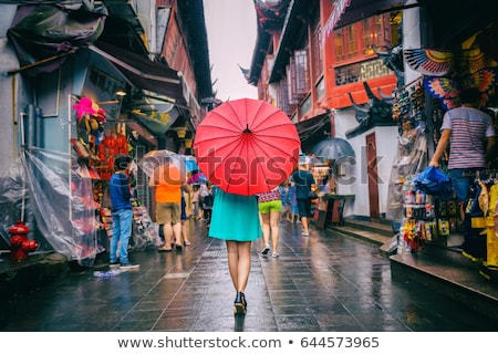 People woman walking in chinatown shopping street. Rainy day girl tourist under red oriental umbrell Stock photo © Maridav