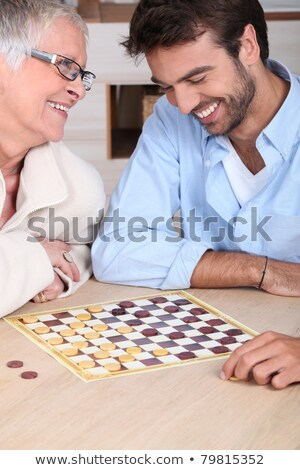 young man playing checkers with older woman Stock photo © photography33