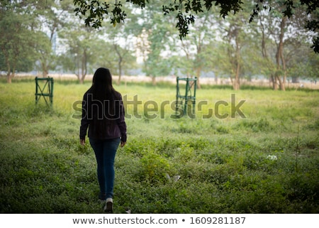 Asian indian woman walking in golden dried field Stock photo © lunamarina