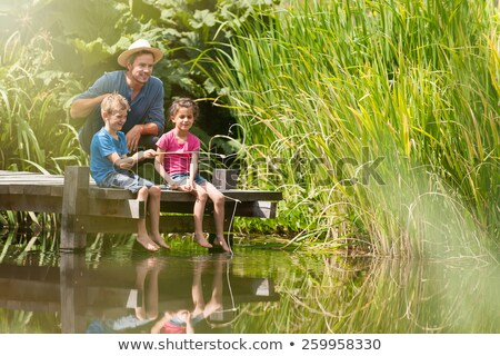 Stock photo: A father and his son fishing.