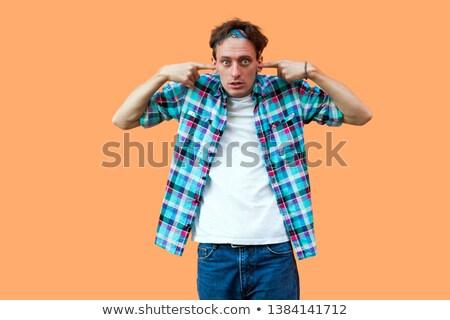 Man blocking his ears and looking at camera stock photo © wavebreak_media