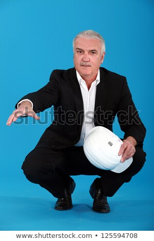 grey haired architect crouching and offering to shake hand stock photo © photography33