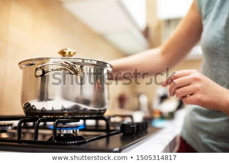 Stock photo: beautiful young woman housewife with a kitchen saucepan pot