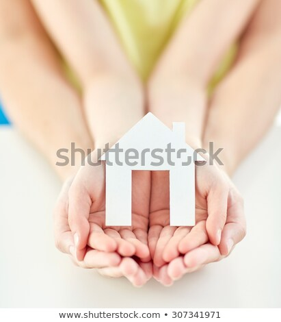 close up of happy girl hands holding paper house stock photo © dolgachov