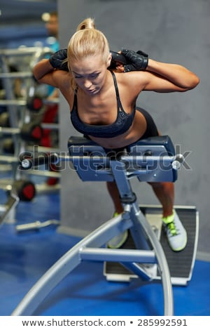 Young woman flexing back muscles on bench Stock photo © deandrobot