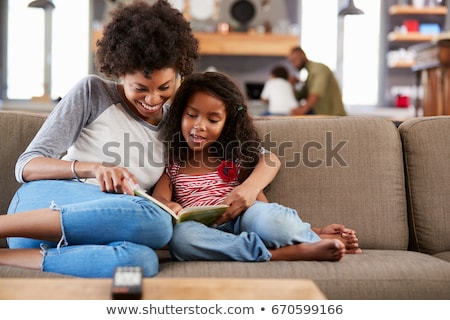 Girl reading book. Child sits in front of an open book Stock photo © orensila