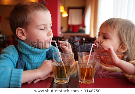 soiled boy drinks juice from glass through straw Stock photo © Paha_L