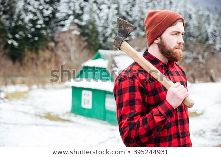 Handsome bearded man holding axe and walking in village Stock photo © deandrobot