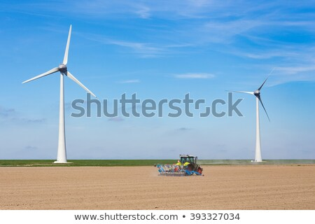 Stockfoto: Farmer On Tractor Sowing In Soil Near Dike And Windmills