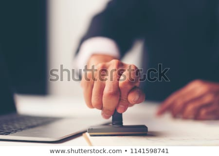 Businessman Stamping Contract Document At Office Desk Stock photo © AndreyPopov