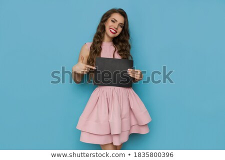 Pretty young lady holding cocktail and pointing Stock photo © deandrobot