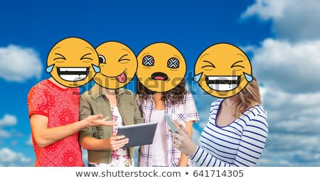 digitally generated image of friends faces covered with emoji using digital tablet and smart phone a stock photo © wavebreak_media