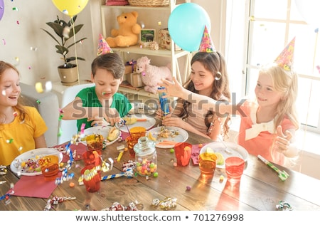 Young boy at party sitting at table with food smiling Stock photo © monkey_business