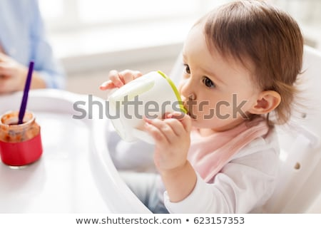 baby drinking from spout cup in highchair at home Stock photo © dolgachov