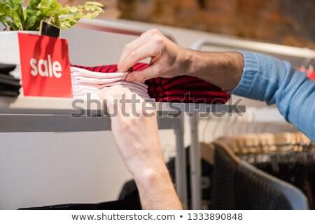 Man Shopping Holding Folded Shirt Stock fotó © O_Lypa