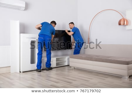 young movers placing television in the living room stock photo © andreypopov