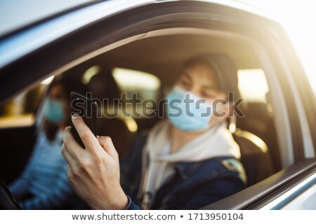 Woman in car checking cell phone Stock photo © IS2