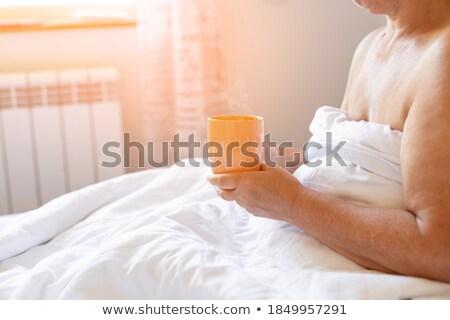 Een beker koffie witte bed goedemorgen Stockfoto © Illia