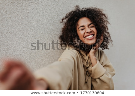 portrait of an excited woman with dark curly hair stock photo © deandrobot